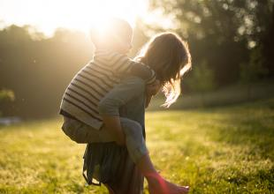 Child having a piggyback in a beautiful sun-lit scene